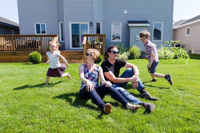 Two happy kids running around their parents in the backyard | stress-free family photography sessions