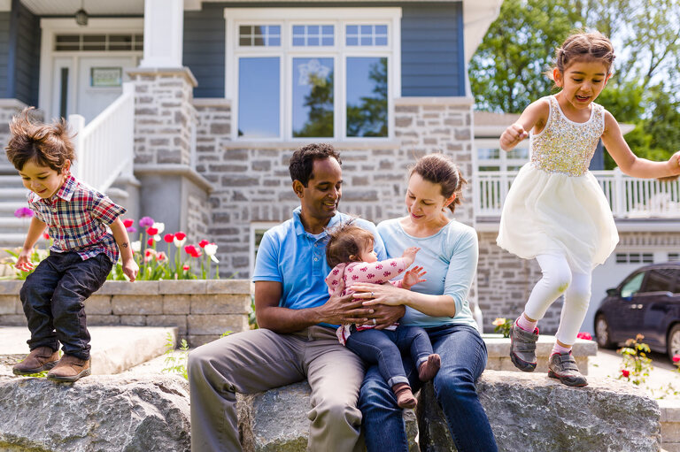Photo of family playing in front of their Ottawa home | stress-free family photography sessions