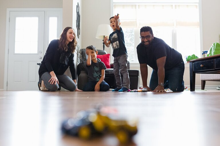 Mom, Dad and two young boys playing with cars on their living room floor | stress-free family photography sessions